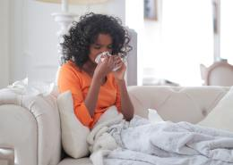 young-black-woman-covered-with-blanket-blowing-nose-3960031